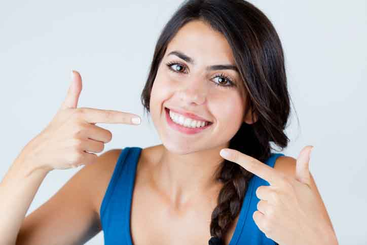 women pointing at here beautiful smile